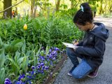 Girl taking notes and studying plants
