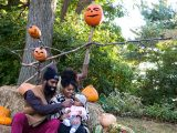 Family sitting on hay bales with pumpkins above them