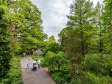 Visitors walking along the ECAG path with green trees surrounding them