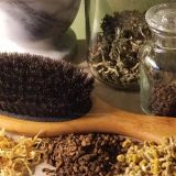 A hair brush surrounded by dried botanicals