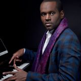 Harold O'Neal wearing a black and blue plaid suit jacket and a purple patterned scarf while playing piano
