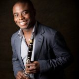 Head shot of Anthony McGill holdig a clarinet on a black backgroud
