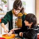 a woman and young boy dressed warmly stirring ingredients together