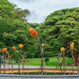 Several pumpkin-headed scarecrows made from fallen brances standing in a reflecting pool with small pumpkins floating around.