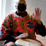 Image of african american man in bright red and gold sweater wearing a face mask holding one hand up while the other is on a large hand drum.