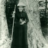 Black and white image of Elizabeth Britton standing outside next to a large tree with a triangular hat on and holding a large stick.