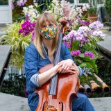 photo of woman Amanda Gookin seated with a cello in front of pink orchids