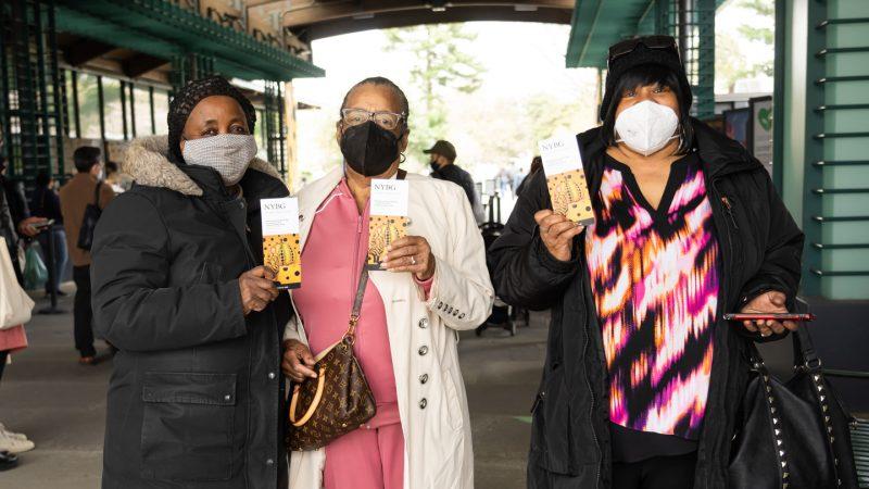 Three women wearing masks and holding ticket vouchers featuring Yayoi Kusama