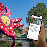 An image of a hand holding a phone in front of a tentacled red and blue statue with a yellow sun-like face and white polka dots.