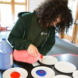 An explainer pouring paint