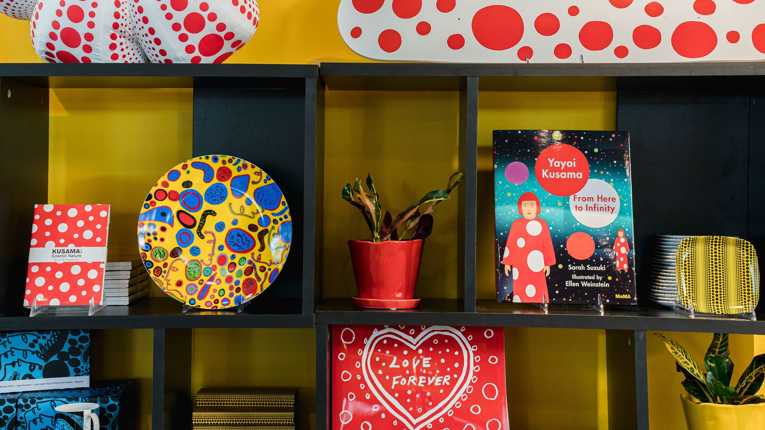 A variety of plates, books, notebooks, and more merchandise from the KUSAMA: Cosmic Nature exhibition, many featuring the art of Yayoi Kusama.