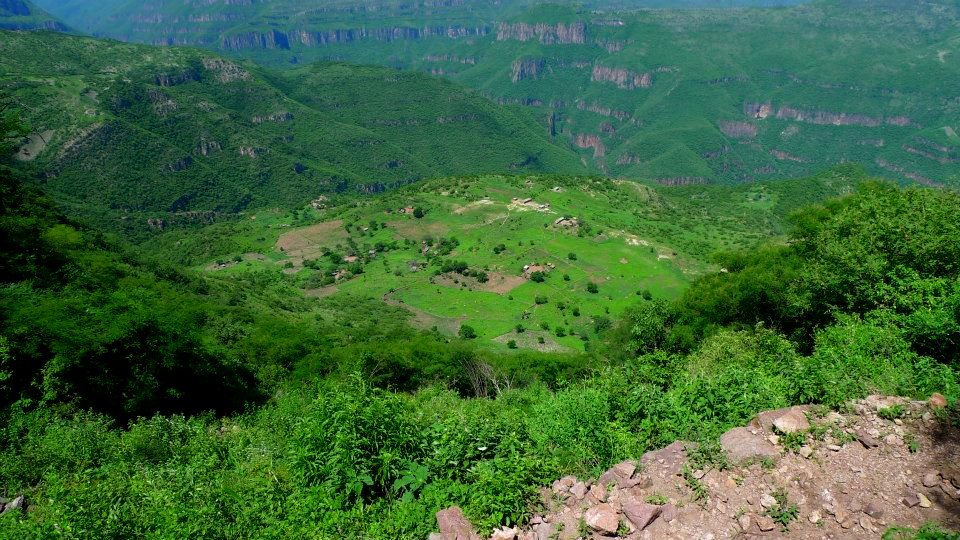Photo from a distance of a small village among green mountains
