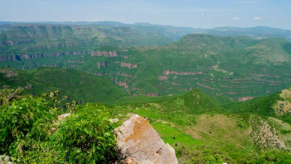 Photo from atop a cliff of green mountains and valleys interspersed with red rock