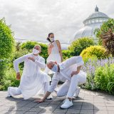 Three people dressed in all white wearing white masks stand in contorted poses together in front of a large glass house in the background with green bushes and plants surrounding them.