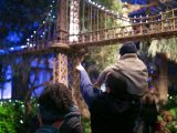 A couple explore the Holiday Train Show after dark, showing their child one of the bridges that passes over head