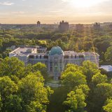 Airborne view of the Bronx borough skyline near sunset, a classical structure surrounded by a forest of trees visible in the foreground, with a domed, patina'd copper structure on top