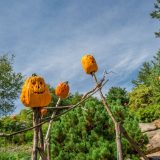 Three sculptures of stick figures with pumpkin heads on top