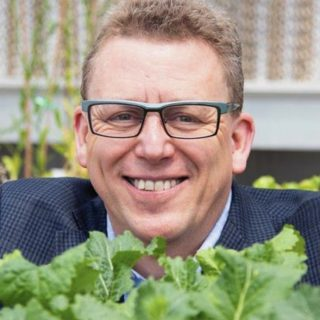 A man in rectangular blue glasses with upturned lips is visible behind a number of young growing plants