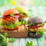 Plant-based burgers in a variety of shapes and colors sit on a cutting board, plants visible in the background
