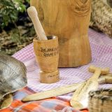 A wooden mortar and pestle sits on a table with various wooden utensils and a turtle shell