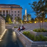 Two people sit at dusk on a series of stone steps leading down into a well-lit water feature, trees surrounding the space and the spike of the Washington Monument rising up in the distance