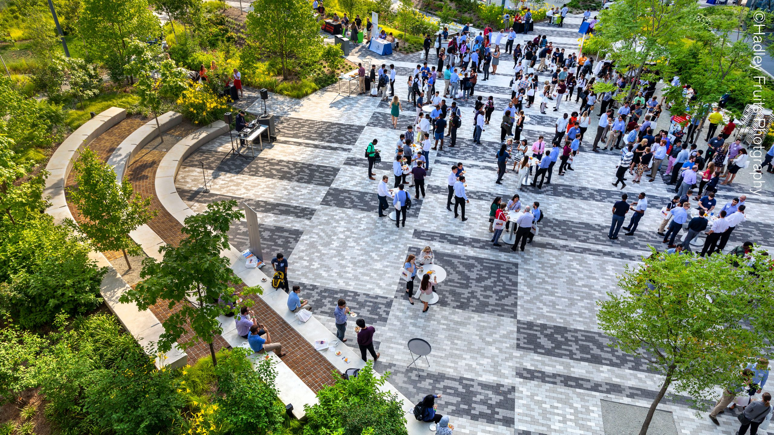 A view of a brick courtyard full of people gathering around standing tables, with trees interspersed throughout the courtyard space and a rich border of terraced cement seating and planted landscapes