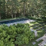 A terraced back yard, hemmed in with open forest, boasts lush green foliage planted around an in-ground swimming pool