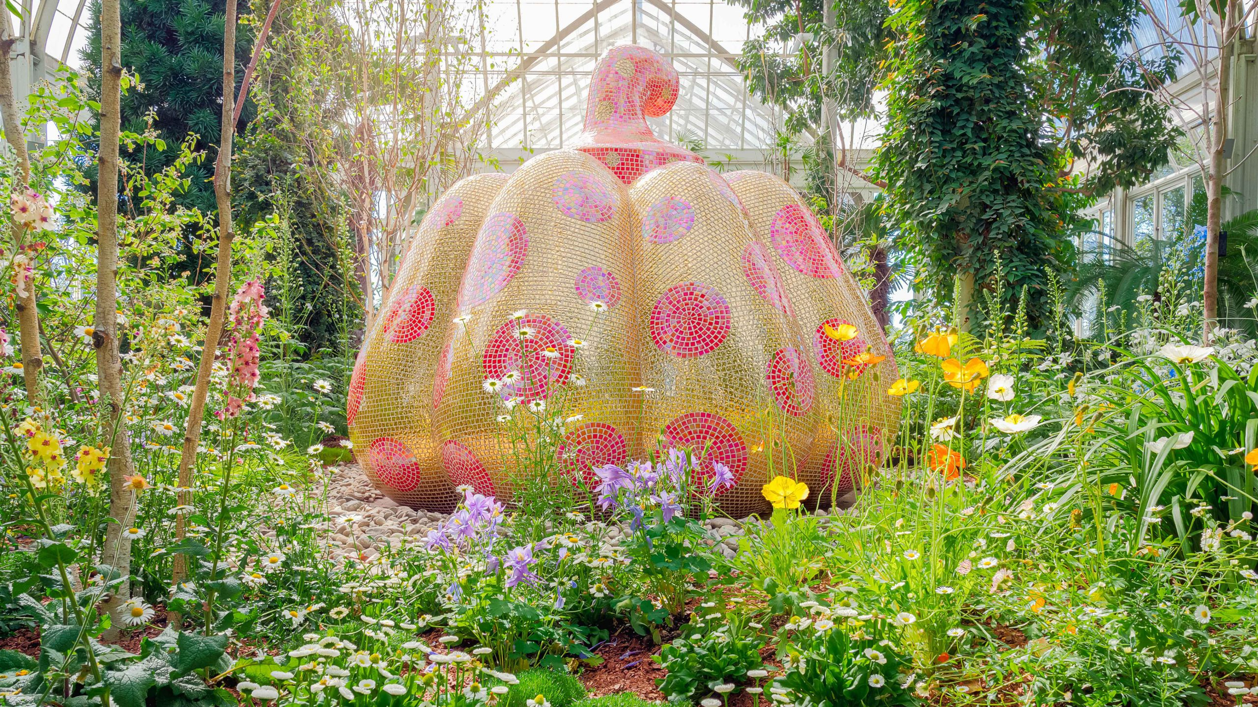 A large pumpkin sculpture covered in yellow mosaic tiles with red mosaic polka dots. Its stem is covered in red mosaic tiles with small yellow mosaic polka dots. The sculpture is nestled into a bed of low-lying flowers and plants, with small trees and vines rising up just behind it.