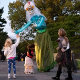 The backs of three small children looking upward to a larger than life skeleton puppet with long white hair, a shiny teal shirt and an olive green skirt.