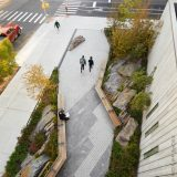 A view from above of an urban greenspace, composed of a slanting cobbled path lined with granite stones, trees, shrubs, grasses, and integral benches