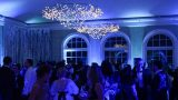 A large crowd of people gathers in a blue-lit ballroom, with chandeliers overhead